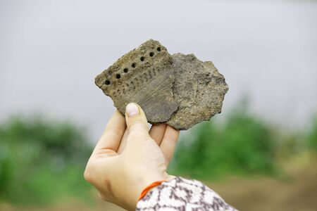 Pieces of ancient clay vessel in the hand of an archaeologist
