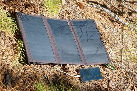 Collapsible solar panel charges a smartphone