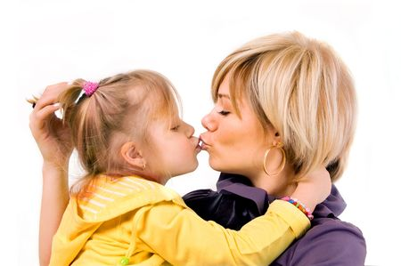 young mother and little daughter is kissed on a white background