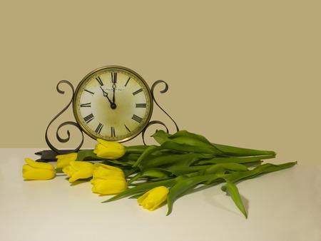 numeros romanos: reloj antiguo muestra 11 horas. tulipanes amarillos se extiende delante de ellos, a la espera.