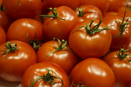 Many ripe tomatoes with green peduncles are heaped