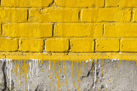 Yellow brick wall with paint stains Stock Photo