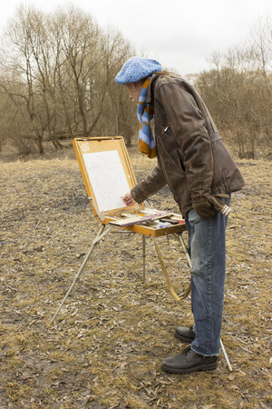 The artist paints an autumn landscape with a pastel on an easel Stock Photo