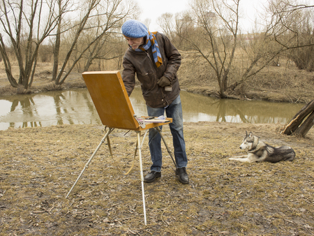 The artist in a beret with an easel paints a landscape in the park