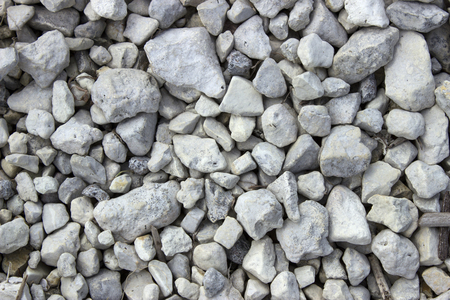 Gray and white lake gravel lies on the shore of the lake