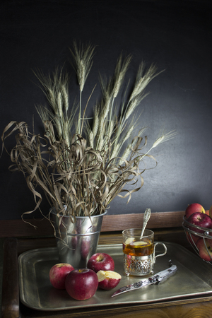 Autumn still life with apples, a glass of tea and a bouquet of dry plants Stockfoto