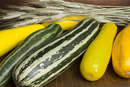 Several colorful zucchini and ears of rye