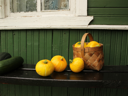 Basket with small pumpkins and squash on the porch of a village house Stockfoto
