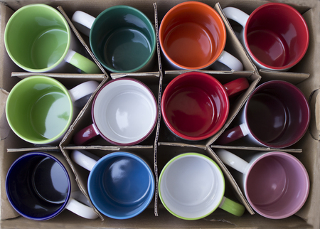 Several new colorful mugs in a carton