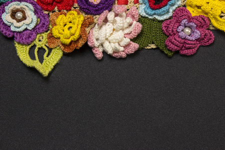 Black background and a row of multicolored knitted flowers on top Stockfoto