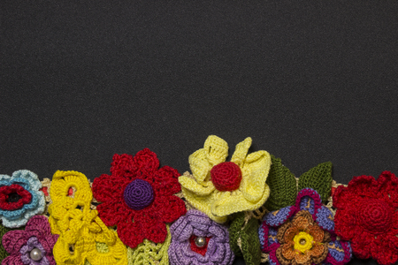 Black background and a row of multicolored knitted flowers from below Stockfoto