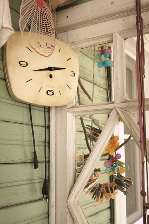 Wall clocks and a bunch of clothes pegs in an old wooden house
