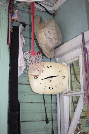 Hallway of an old wooden house with a clock and a hat on a hook Stockfoto
