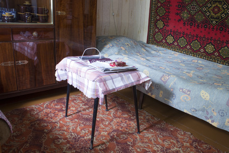 The interior of the room in the old Russian house. Bed, carpets, coffee table with magazines, sideboard with dishes