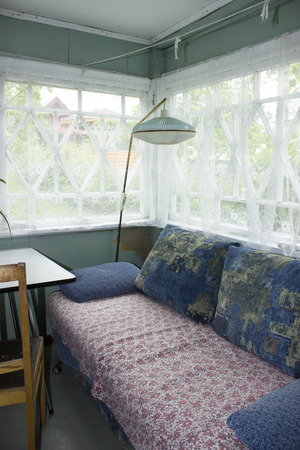 Veranda in an old village house with a sofa and floor lamp