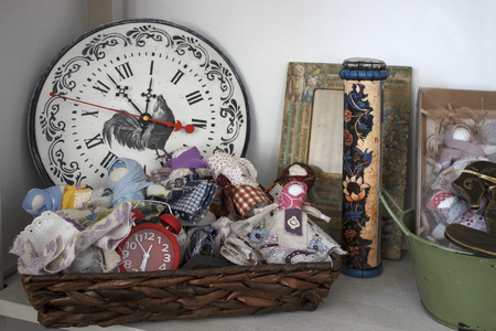 Basket with rag dolls, red alarm clock, a clock with a rooster