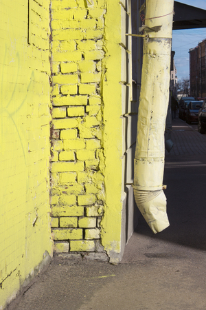 Yellow brick house corner and drainpipe on a sunny day