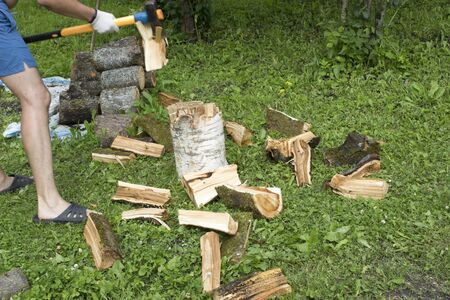 A man chops firewood. The blow of the ax split the log Stockfoto