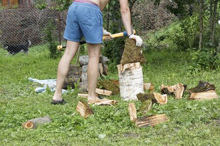 A man chops firewood in the country in the summer in hot weather Stockfoto