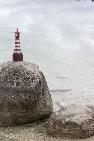 Toy lighthouse stands on a stone on the shore of the north lake Stock fotó