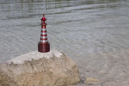 A toy lighthouse stands on a stone by the lake, lit by the sun. Stock fotó