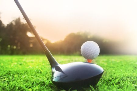 Golf clubs and golf balls on a green lawn in a beautiful golf course with morning sunshine.Ready for golf in the first short.Sports that people around the world play during the holidays for health.