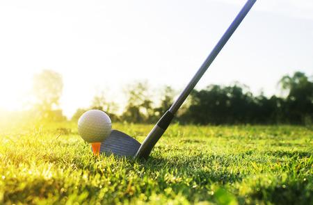 Kije golfowe i piłki golfowe na zielonym trawniku na pięknym polu golfowym z porannym słońcem.Gotowy do gry w golfa w pierwszym skrócie.Sporty, w które ludzie na całym świecie grają podczas wakacji dla zdrowia. Zdjęcie Seryjne