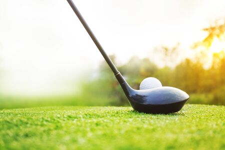 Golf clubs and golf balls on a green lawn in a beautiful golf course with morning sunshine.Ready for golf in the first short.Sports that people around the world play during the holidays for health. Foto de archivo