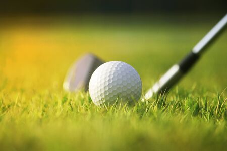 Golf clubs and golf balls on a green lawn in a beautiful golf course with morning sunshine.Ready for golf in the first short.Sports that people around the world play during the holidays for health. Banco de Imagens