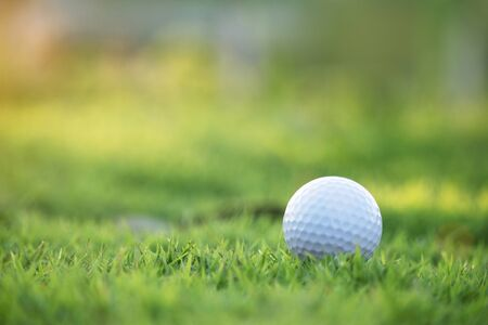 Golf ball is on a green lawn in a beautiful golf course with morning sunshine.Ready for golf in the first short.Sports that people around the world play during the holidays for health. Stock Photo