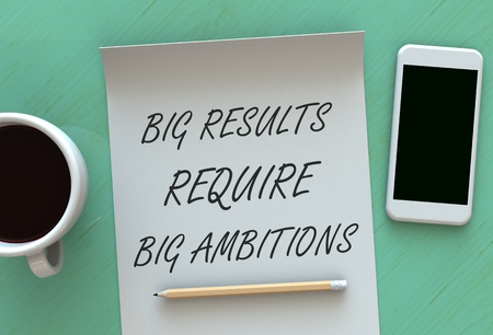require: Big Results Require Big Ambitions, message on paper, smart phone and coffee on table Stock Photo