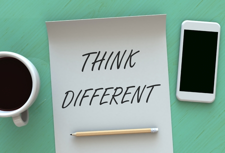 differently: Think Different, message on paper, smart phone and coffee on table
