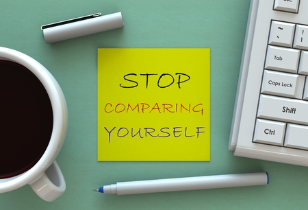 comparing: STOP COMPARING YOURSELF, message on note paper, computer and coffee on table
