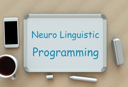 linguistic: Neuro Linguistic Programming, message on whiteboard, smart phone and coffee on table Stock Photo