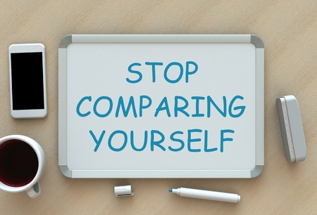 comparing: STOP COMPARING YOURSELF, message on whiteboard, smart phone and coffee on table