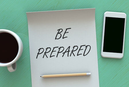 be prepared: BE PREPARED, message on paper, smart phone and coffee on table