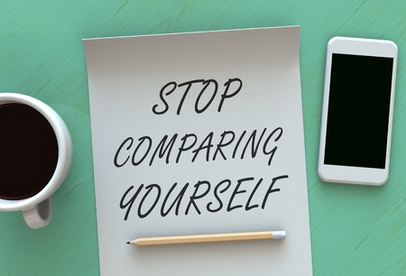 comparing: STOP COMPARING YOURSELF, message on paper, smart phone and coffee on table Stock Photo