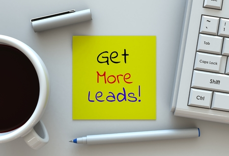 Get More Leads, message on note paper, computer and coffee on table Stock Photo