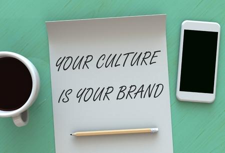 Su cultura es su marca, mensaje en el papel, teléfono inteligente y café en la tabla, 3D
