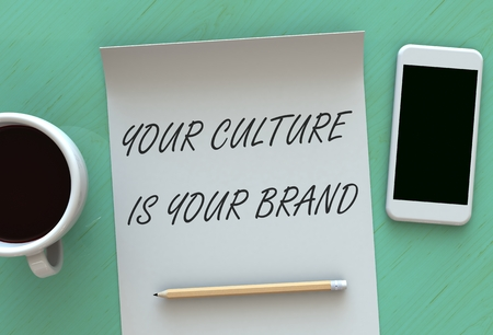 identidad cultural: Your Culture Is Your Brand, message on paper, smart phone and coffee on table, 3D rendering Foto de archivo