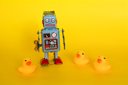 Vintage tin toy robot and small ducklings isolated on a yellow background.