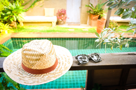 Sunglasses with vintage straw hat fasion on wooden table, Blur background for vintage resort hotel, Concept Summer