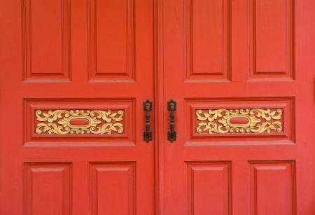 Old brass handle on red  wood door. photo