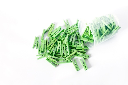 clothespegs: Green clothes-pegs scatter  on  white floor. Stock Photo