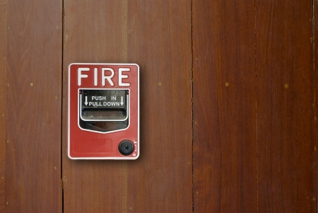 Fire alarm manual pull station on wood walls. photo
