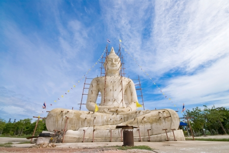 Buddha statue with blue sky and clouds under construction photo