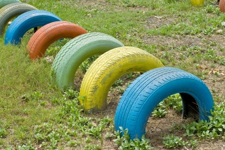 old  tires with colorful paint on a playground photo