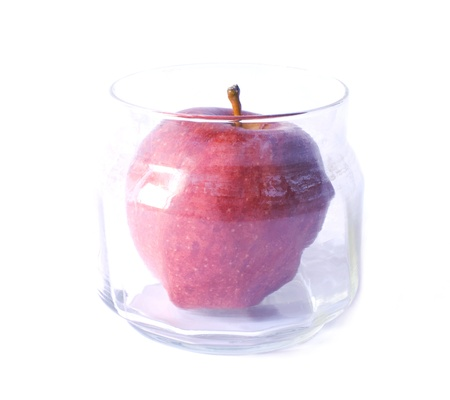 red apple put into a glass jar Stock Photo