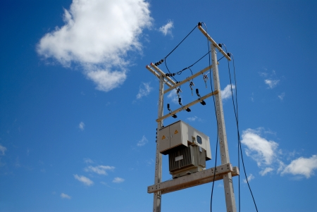 electrical transformer on pole with blue sky background photo