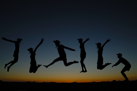 silhouette of  people jumping at sunrise photo